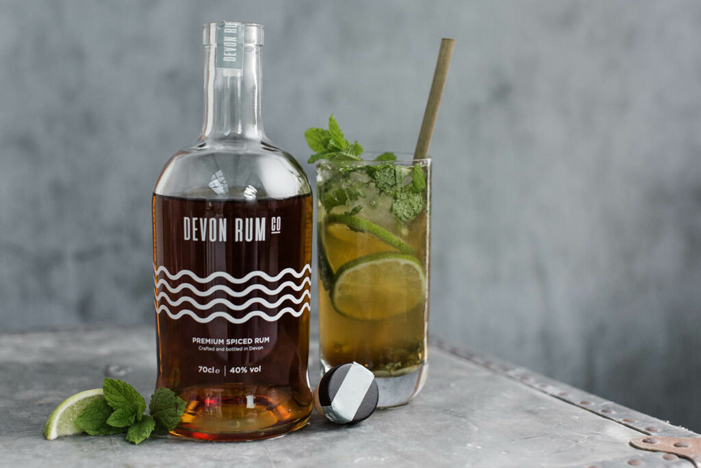 OPen bottle of Devon Rum with a mixed mojito cocktail next to it
