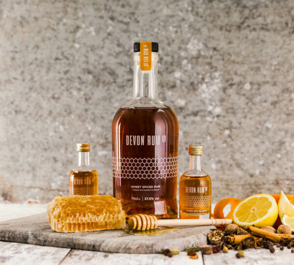 Bottle of Honey Spiced Rum surrounded by citrus fruit and honeycomb