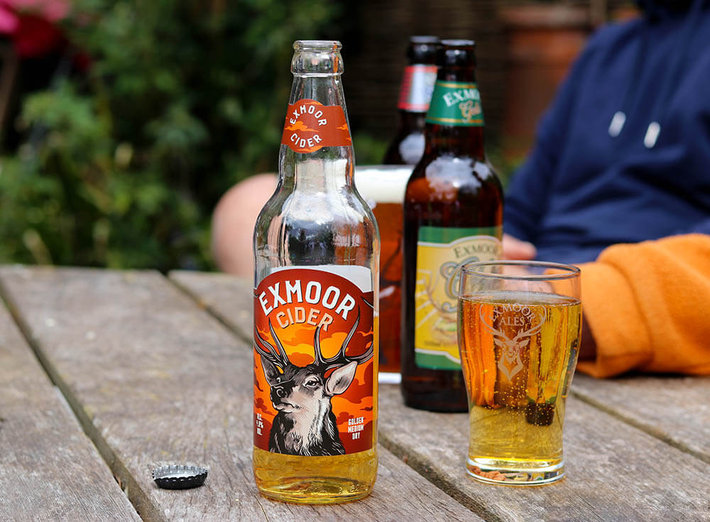 Exmoor Cider bottle and full glass of cider on a garden table